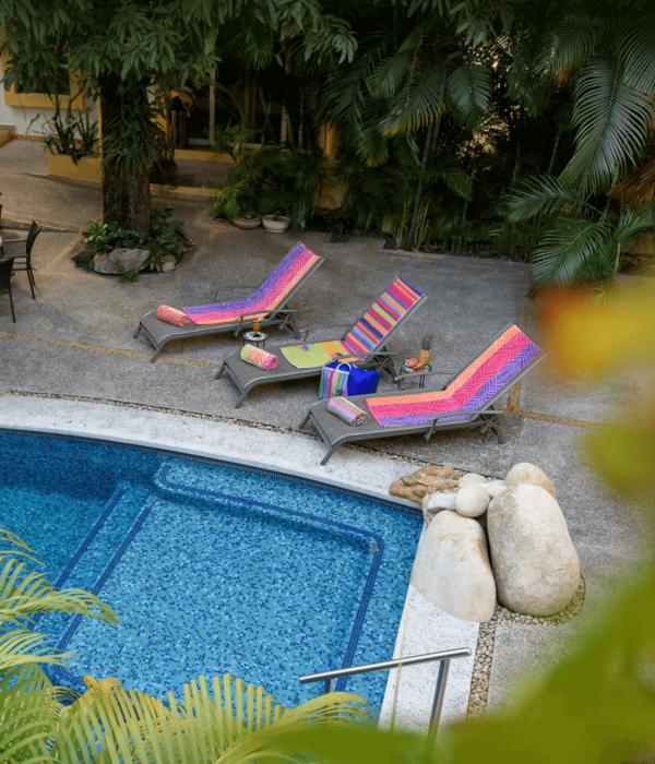 Three lounge chairs by the Hacienda Alemana poolside